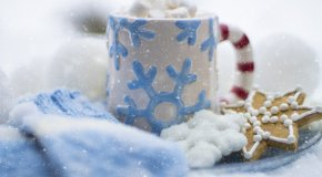 Mug of cocoa, mittens, and snowflake cookie