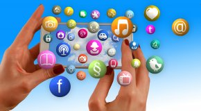 Hands with cell phone and social network icons