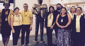 Office staff members dressed in black and gold